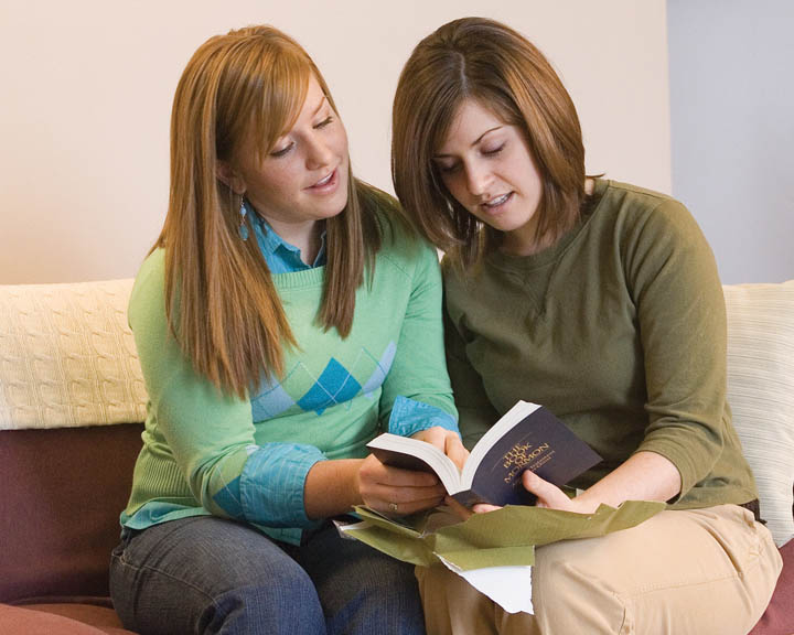 A LDS member sharing the Book of Mormon with a friend