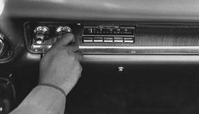 A man turns on a fifties style car radio