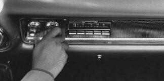 A man turns on a fifties style car radio