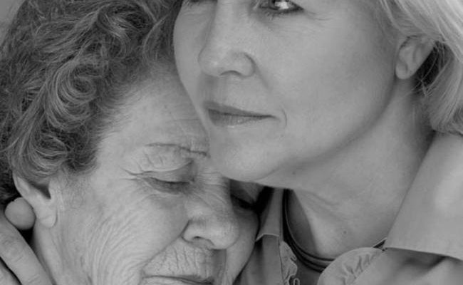 A daughter comforts her elderly mother