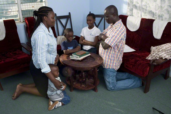 Ghana family kneel in prayer