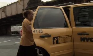 Woman enters a taxi cab in New York City