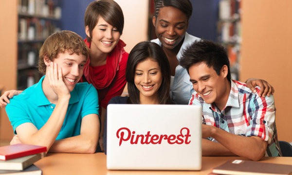 Several young adults surround a computer using Pinterest