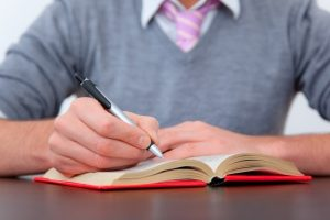 Man writes in a journal