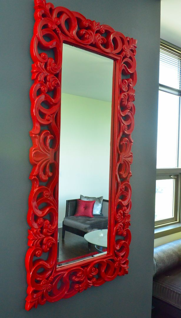 Ornate red mirror reflects Black Couch