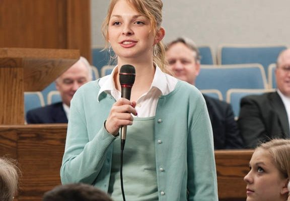 girl holds a microphone speaking at church on sunday