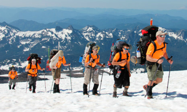 Boys climbing a mountain on snowshoes