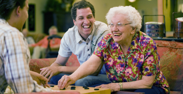 elderly woman playing checkers with young men
