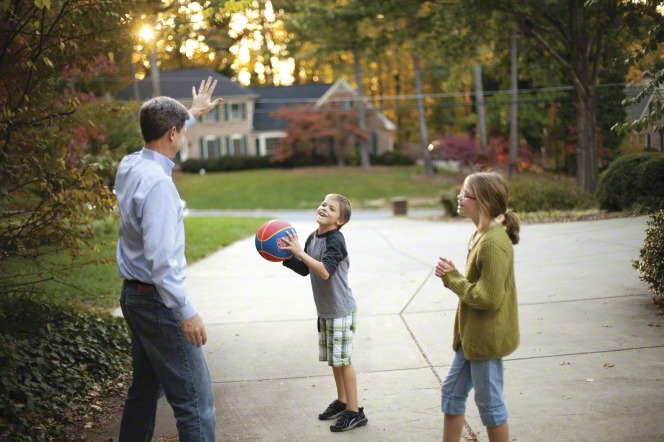 father and children playing basketball