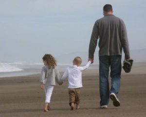 Dad and kids walking on the beach
