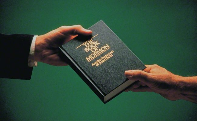 man giving book of mormon