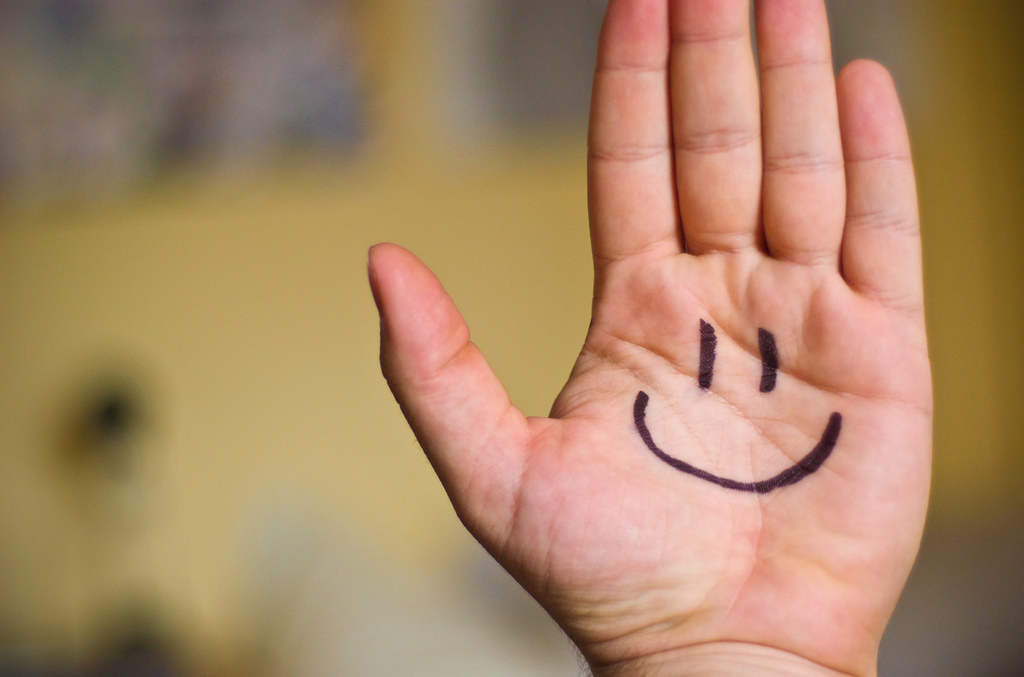 Smiley face drawn on a hand reminds us to be happy