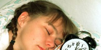 sleeping girl with alarm clock next to her