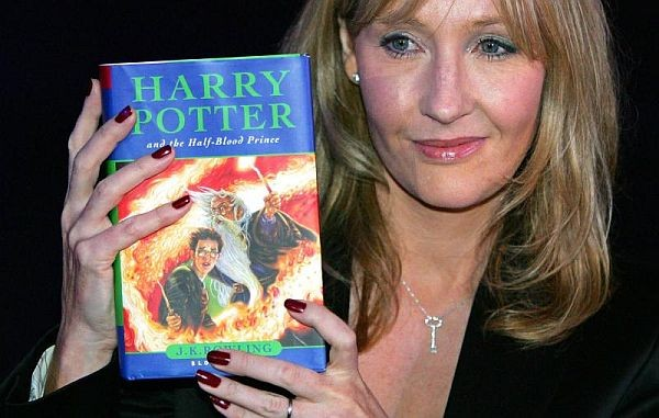 JK Rowling holds up a Harry Potter book