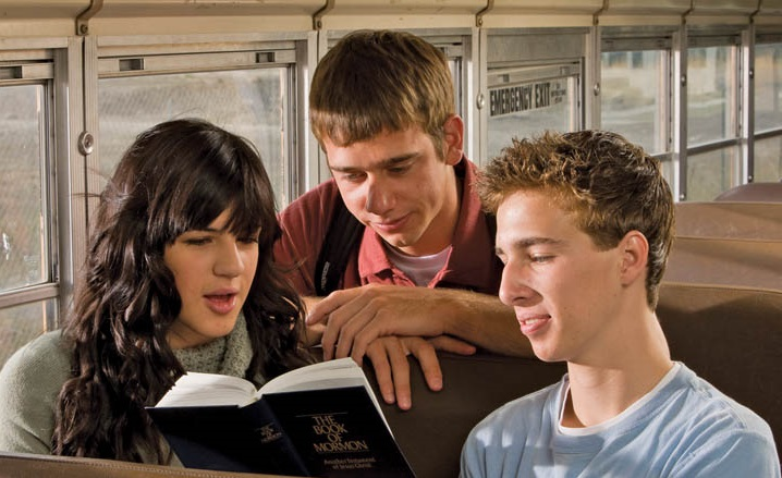 Teens reading the Book of Mormon on a bus