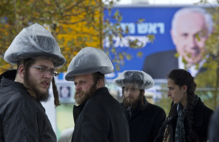 ultra-orthodox Jews covering their hats in the rain
