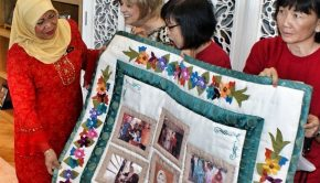 Women leaders in Malaysia present a quilt as a token of appreciation to the minister of women, family, and community development.