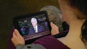 Woman watches conference on her tablet