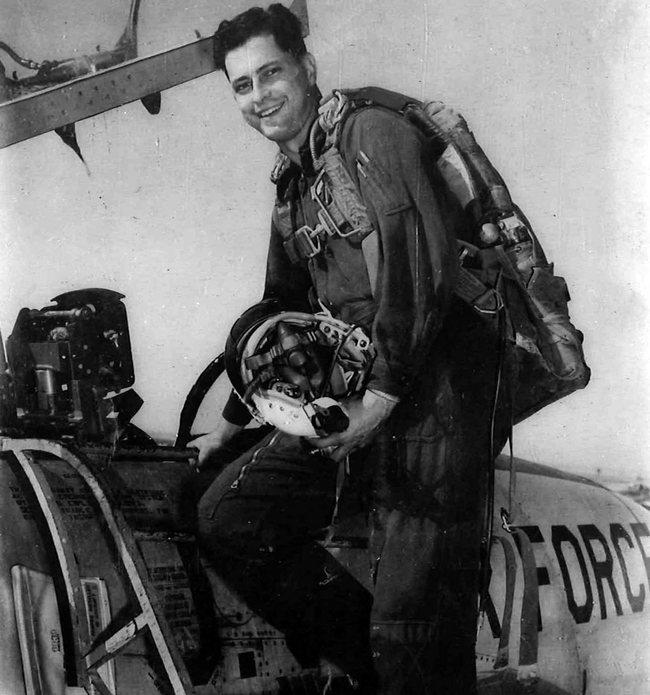 Robert D. Hales climbing into a plane cockpit