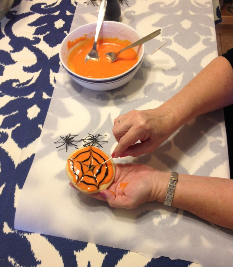 Using a toothpick on cookie icing to create a spider web design