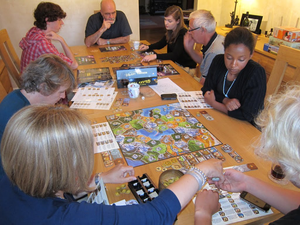 Playing tabletop games - Mormon Friends And Neighbors Playing Board Games Around A Table