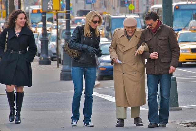 Adults assisting an elderly man across a street