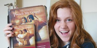 Young adult woman holding well used Preach My Gospel Missionary manuals