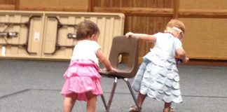 Two toddlers help each other across a room