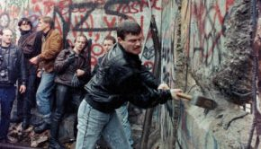 "Behind the Wall: Then & Now"" – change to, ""East German citizens assist in breaking down the Berlin Wall with mallets"