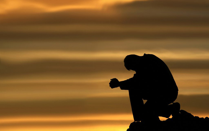 A man kneels on a mountain and prays