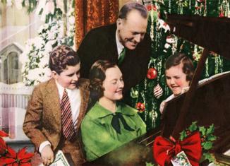 Family gathered around piano singing Christmas songs