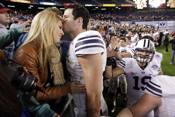 BYU football player embraces wife on field sideline