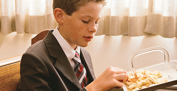 Young man partaking of the sacrament bread