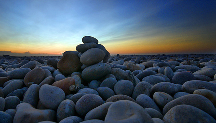 photo of stacked stones in front of a sun rise