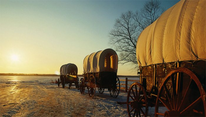 Pioneer wagons travel down snowy trail