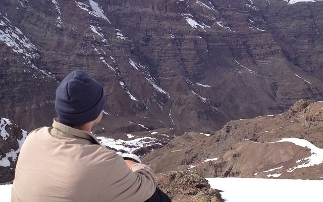Man sitting in mountains contemplating