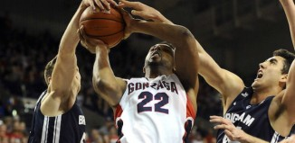 Two BYU defenders block Gonzaga player's shot in basketball game