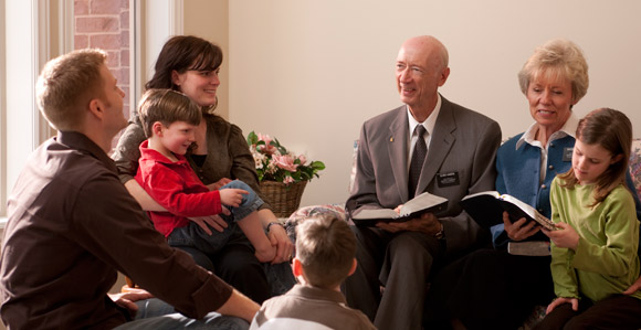 """Senior missionary couple teaching a young family the gospel"""