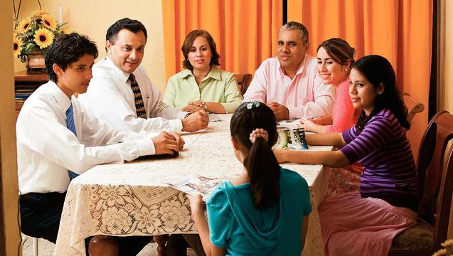 A family gathered around a table being taught