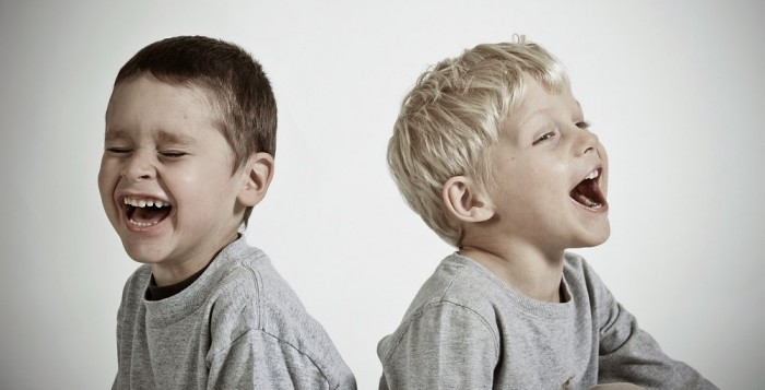 Two boys sitting by each other laughing