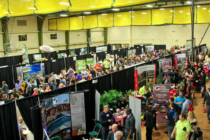 Lots of people looking at booths in a gym at the national landscape competition
