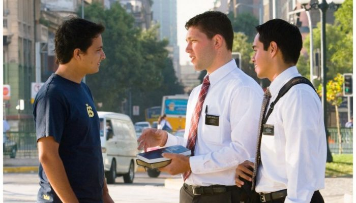 Two male Mormon missionaries talking with a young man on the street