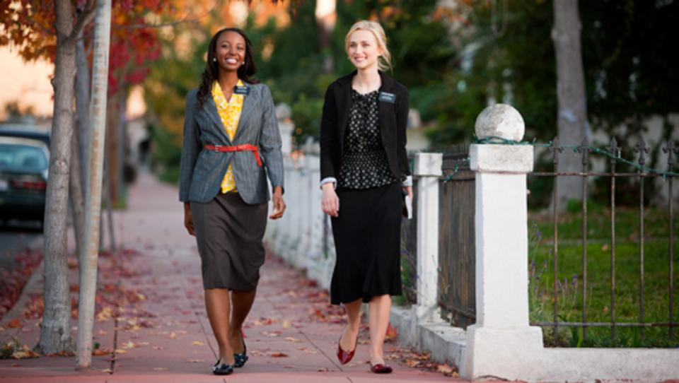 Two LDS women missionaries walking down the sidewalk