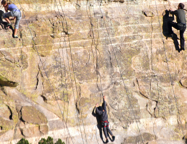 people climbing up a rock wall