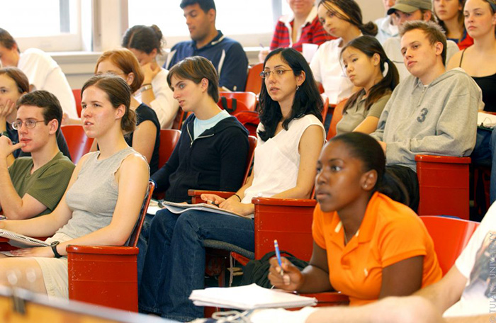 College students sitting in a classroom listening to a teacher
