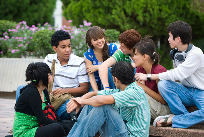 Group of teenagers sitting down talking with each other