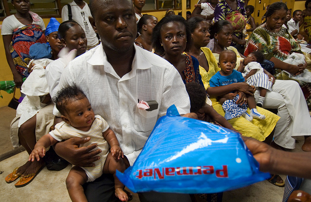 A father receiving a donated mosquito net for his family