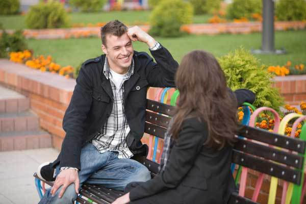 A man meeting a woman on a park bench