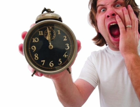 man holding a clock freaking out because he is running out of time. Image via todayfm.com