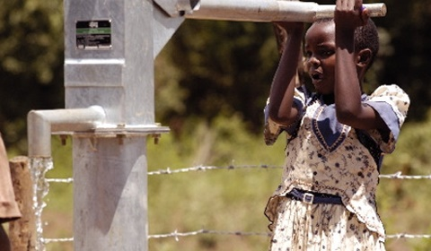 Girl pumping water from a charity built water well